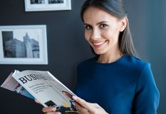 Cute positive trendy girl is holding journal. Keep abreast of latest news. Portrait of happy gorgeous young woman is standing in office with open business royalty free stock photos
