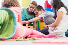 Pre-school boy cooperating with kids under guidance of kindergar. Cute pre-school boy cooperating with his colleagues at the construction of a structure, made of royalty free stock images