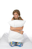 Cute pre-teen girl on mattress holding pillow Stock Photos
