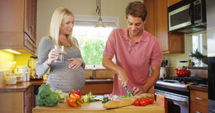 Cute pregnant couple in the kitchen. At home stock photography