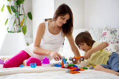 Cute pregnant mother and child boy playing together indoors Stock Image