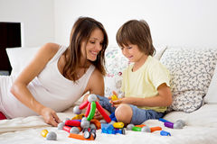 Cute pregnant mother and child boy playing together indoors Royalty Free Stock Images