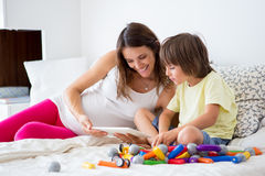 Cute pregnant mother and child boy playing together indoors Stock Images
