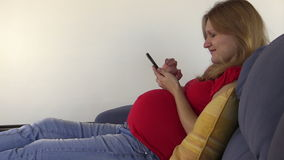Cute pregnant woman browse photos and internet with smart phone stock footage