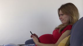 Cute pregnant woman browse photos and internet with smartphone stock video footage