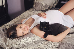 Cute pregnant woman lying in bed with black cat. Stock Photos