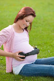 Cute pregnant woman putting headphone on her belly Royalty Free Stock Photography