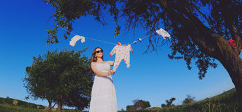 Cute pregnant woman wearing white dress Stock Photography