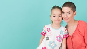 Cute preschool age girl with her mother, young cancer patient in remission. Cancer patient and family support. Cute preschool age girl with her mother, young Royalty Free Stock Images