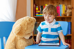 Cute preschool boy playing with tablet computer in his room at h Royalty Free Stock Photos