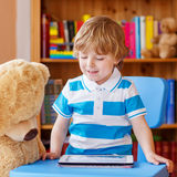 Cute preschool boy playing with tablet computer in his room  Stock Photography