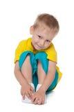 Cute preschool boy. A cute preschool boy sits on the white background royalty free stock image