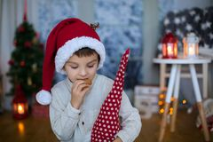 Cute preschool child, boy, reading a book and eating cookies at. Home, while snowing outdoors Stock Photo