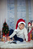Cute preschool child, boy, reading a book and eating cookies at. Home, while snowing outdoors Stock Images