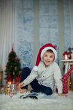 Cute preschool child, boy, reading a book and eating cookies at. Home, while snowing outdoors Royalty Free Stock Image
