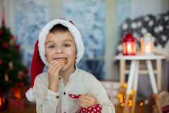 Cute preschool child, boy, reading a book and eating cookies at. Cute preschool , boy, reading a book and eating cookies at home, while snowing outdoors Stock Photography