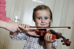 Cute preschool girl learning violin playing Stock Photo
