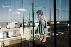 Childhood concept. Little cute preschool girl on glass balcony stock photography