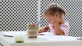 Cute preschool girl sitting by the white table and drawing something by pencil stock video footage