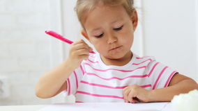 Cute preschool girl sitting by the white table focused on drawing something. Close-up portrait of cute preschool girl sitting by the white table focused on stock video footage