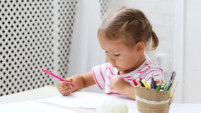 Cute preschool girl sitting by the white table focused on drawing something. Cute preschool girl sitting by the white table focused on drawing something in stock video