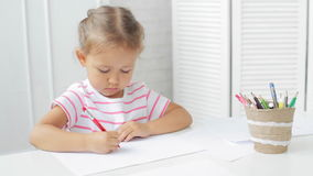 Cute preschool girl sitting by the white table focused on drawing something. Cute preschool girl sitting by the white table focused on drawing something in stock video footage