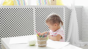 Cute preschool girl sitting by the white table focused on drawing something. Cute preschool girl sitting by the white table focused on drawing something in stock footage