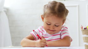 Cute preschool girl sitting by the white table focused on drawing something. stock video footage