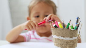 Cute preschool girl sitting by the white table focused on drawing something. stock footage