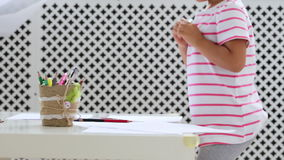 Cute preschool girl sitting by the white table focused on drawing something. Cute preschool girl standing by the white table and preparing for drawing, than she stock video footage