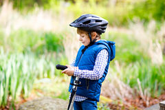 Cute preschool kid boy riding on bicycle in park Stock Photography