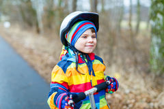 Cute preschool kid boy riding on scooter in park Royalty Free Stock Images
