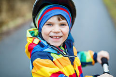 Cute preschool kid boy riding on scooter in park Stock Images