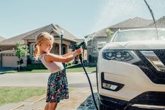 Girl washing car on driveway in front house on sunny summer day