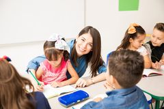 Cute preschool teacher helping a student. Good looking Hispanic female preschool teacher enjoying her job and teaching students in a classroom royalty free stock photography