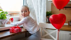 Cute preschooler girl celebrating 6th birthday. Girl with cheeky smile eating her birthday cupcake in the kitchen. stock image