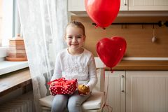 Cute preschooler girl celebrating 6th birthday. Girl holding her birthday cupcake and beautifully wrapped present. stock images