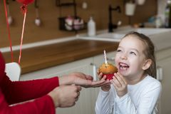 Cute preschooler girl celebrating 6th birthday. Mother giving daughter birthday cupcake with a candle. Childrens birthday party. royalty free stock image