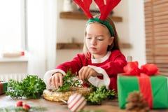 Cute preschooler girl dressed in reindeer costume wearing reindeer antlers making christmas wreath in living room. Christmas decor. Ation family fun concept stock image