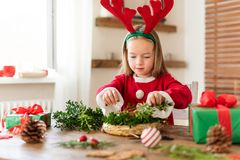 Cute preschooler girl dressed in reindeer costume wearing reindeer antlers making christmas wreath in living room. Christmas decor. Ation family fun concept stock photography