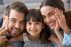 Cute preschooler girl hug parents posing for picture together stock photo