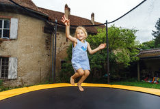 Cute preschooler girl jumping on trampoline Royalty Free Stock Images