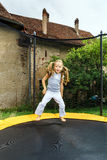 Cute preschooler girl jumping on trampoline Royalty Free Stock Photos