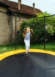 Cute preschooler girl jumping on trampoline Royalty Free Stock Photography