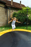 Cute preschooler girl jumping on trampoline Royalty Free Stock Photo