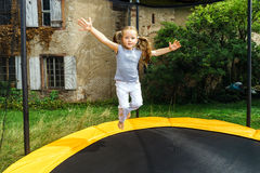 Cute preschooler girl jumping on trampoline Stock Images