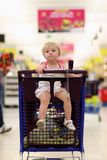 Cute preschooler girl sitting in shopping cart Stock Photography