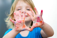 Cute preschooler girl with smile showing colored hands. Selectiv Royalty Free Stock Photos