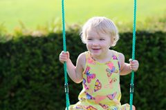 Cute preschooler girl swinging outdoors Stock Photography