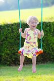 Cute preschooler girl swinging outdoors Royalty Free Stock Image